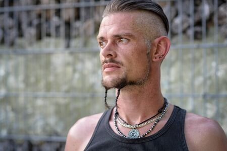 Tough guy with sparrow beard, undercut and black rip shirt standing thoughtful in front of a wall of stones Zdjęcie Seryjne