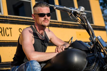 Tough guy with sparrow beard, undercut, black rip shirt and sun glasses lolling on his chopper motorcycle in front of a yellow, American school bus. Zdjęcie Seryjne