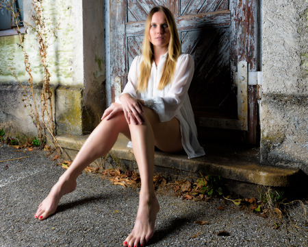 hot pants: Blond woman in hot pants sitting in front of an weathered door