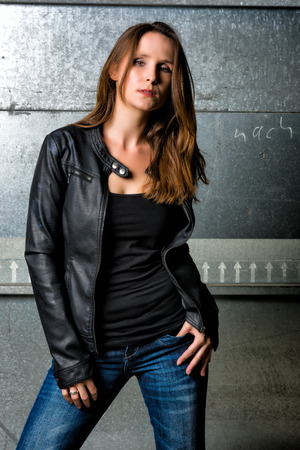Trendy Woman with long hair in blue jeans posing in the grungy underground Banco de Imagens