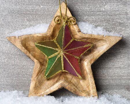 estrellas de navidad: Estrella de madera cubierto de nieve con el ornamento de la Navidad.