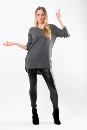 black pants: Blond fashion woman in slim black pants posing in front of white background Stock Photo