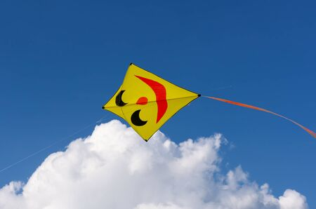 rise: Yellow kite with smiling face isolated on blue sky.