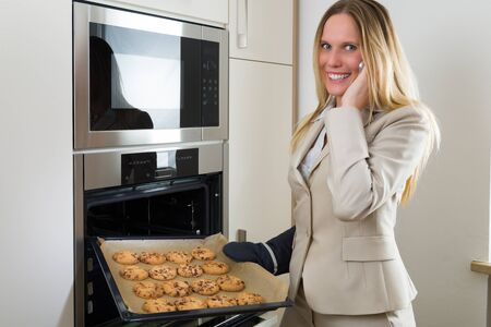 woman baking: Double burden: attractive business woman baking cookies in a modern kitchen and having sim