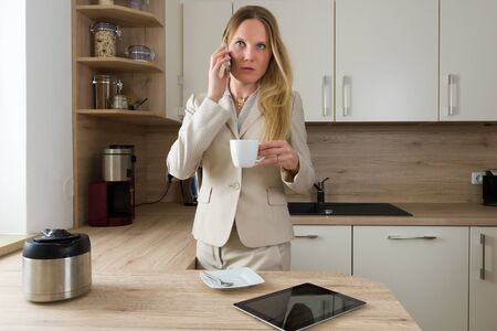 liberated: Multitasking in the kitchen: Attractive, Caucasian business woman drinking simultaneously coffee and having a phone call. Modern Lifestyle