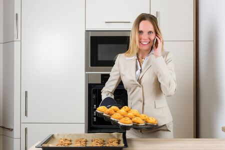 simultaneously: Double burden: attractive business woman baking cupcakes in a modern kitchen and having simultaneously a phone call Stock Photo