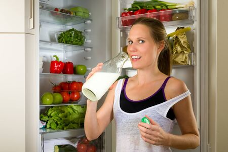 gym dress: Sporty, Caucasian woman drinking milk for healthy nutrition in front of a refrigerator
