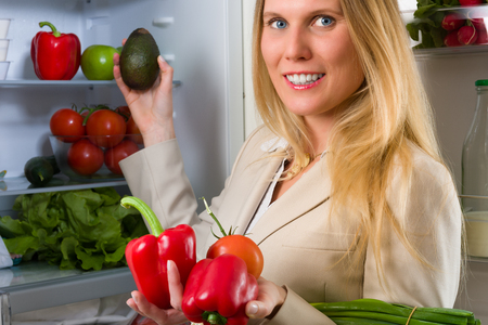 liberated: Attractive business woman showing vegetables for healthy eating in front of a refrigerator