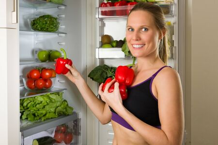 gym dress: Sporty, Caucasian woman showing vegetables for healthy eating in front of a refrigerator
