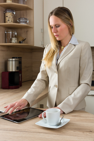 liberated: Attractive, Caucasian business woman working with a tablet in the kitchen. Modern Lifestyle