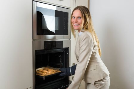 liberated: Double burden: attractive business woman baking cookies in a modern kitchen Stock Photo