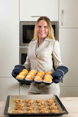 liberated: Double burden: attractive business woman baking cupcakes in a modern kitchen Stock Photo