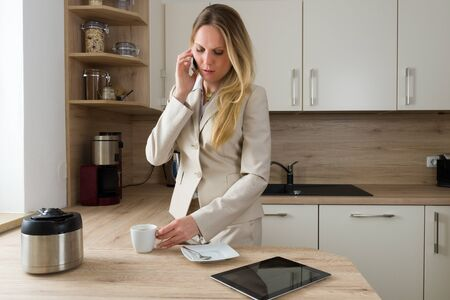 simultaneously: Multitasking in the kitchen: Attractive, Caucasian business woman drinking simultaneously coffee and having a phone call. Modern Lifestyle