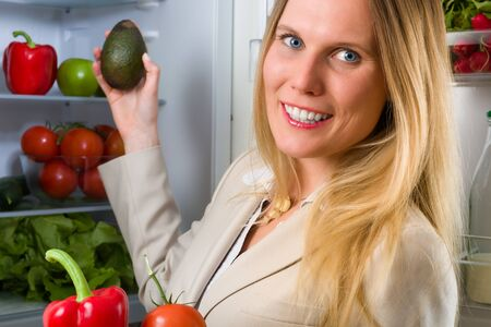 fair haired: Attractive business woman showing vegetables for healthy eating in front of a refrigerator