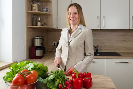 liberated: Attractive Caucasian woman in business suite cutting vegetables in the kitchen, showing the double burden of modern life