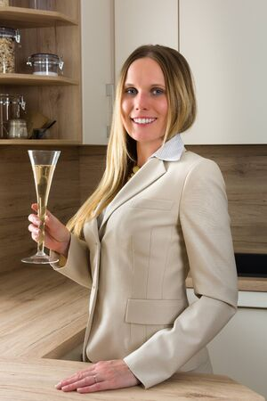 liberated: Time to celebrate: business woman with a glass of champagne relaxing in a modern kitchen