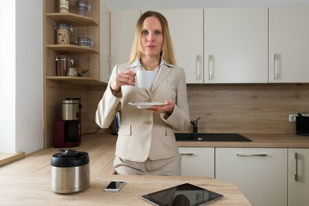 liberated: Attractive Caucasian woman in business suite with smartphone and tablet drinking coffee in the kitchen. Modern Lifestyle Stock Photo