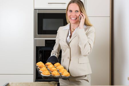 woman baking: Double burden: attractive business woman baking cupcakes in a modern kitchen and having simultaneously a phone call Stock Photo