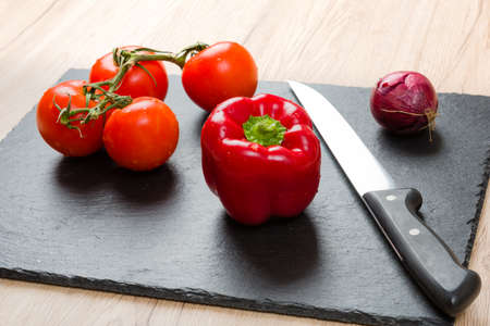 Black slate cutting board with knife and vegetables, ready for slicing