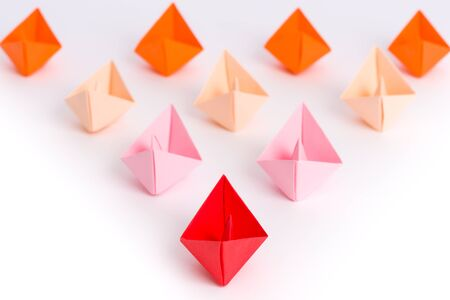 overwhelm: Fleet of origami paper ships in triangle shape isolated on white - like a overwhelming flood