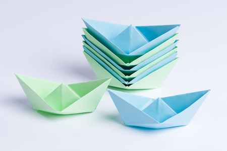 staple: Staple of blue and green origami paper ships symbolizing production process. Stock Photo