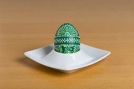 egg cup: Sorbian Easter egg sitting in white egg cup. Old, traditional handcraft of the Sorbian people, an ethnic minority living in Germany
