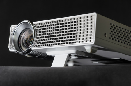 Close up on the foot of a white mini home cinema LED projector.