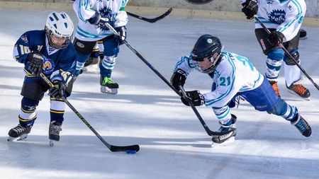 Fuerstenfeldbruck, Bavaria, Germany - 06. February 2016: German Kids playing ice hockey. Age is about 10 years. Player with white shirt on the right is trying a last minute defense action. 報道画像