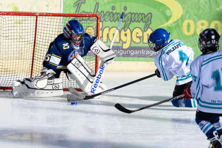 about age: Fuerstenfeldbruck, Bavaria, Germany - 06. February 2016: German Kids playing ice hockey. Age is about 10 years. Two players in white are ready for a goal, but the goal keeper fights to prevent it.