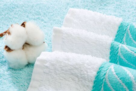 natural materials: Stack of bath towels with cotton blossom, showing use of natural materials Stock Photo