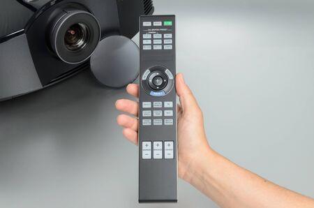 Enorme zwarte home cinema projector, met de hand de presentatie van de afstandsbediening. Stockfoto