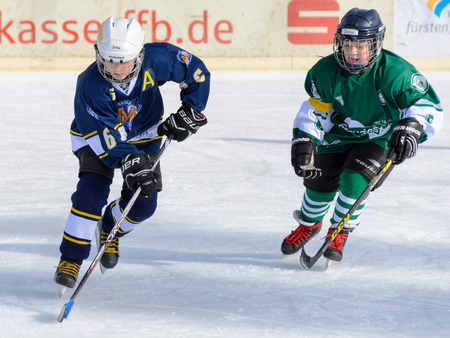 about age: Fuerstenfeldbruck, Bavaria, Germany - 06. February 2016: German Kids playing ice hockey. Age is about 10 years. Players are fighting for the puck.