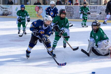 age 10: Fuerstenfeldbruck, Bavaria, Germany - 06. February 2016: German Kids playing ice hockey. Age is about 10 years. Close up fight near the goal.