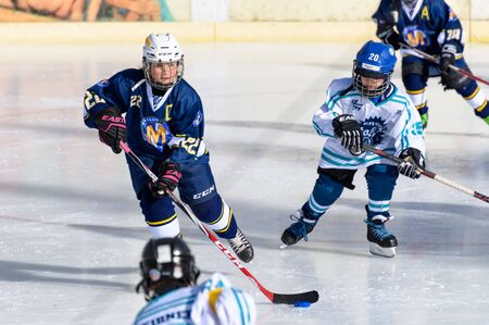 age 10: Fuerstenfeldbruck, Bavaria, Germany - 06. February 2016: German Kids playing ice hockey. Age is about 10 years. Single blue player maneuvering through heavy defense. Editorial