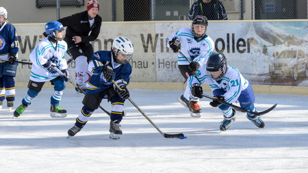 age 10: Fuerstenfeldbruck, Bavaria, Germany - 06. February 2016: German Kids playing ice hockey. Age is about 10 years. Blue player is approaching the goal - defense jumps after the puck.