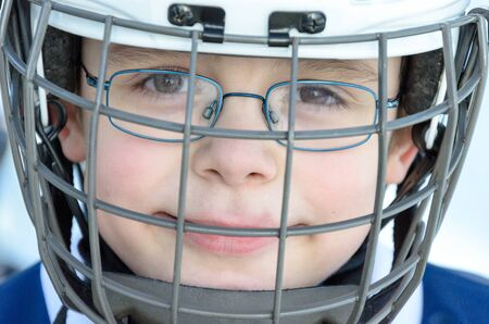 about age: Fuerstenfeldbruck, Bavaria, Germany - 06. February 2016: German Kids playing ice hockey. Age is about 10 years. Head shot of one player. Editorial