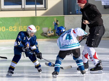 age 10: Fuerstenfeldbruck, Bavaria, Germany - 06. February 2016: German Kids playing ice hockey. Age is about 10 years. Kick-off fight for the puck.
