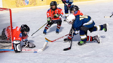 age 10: Fuerstenfeldbruck, Bavaria, Germany - 06. February 2016: German Kids playing ice hockey. Age is about 10 years. Successful defense near the goal. Editorial