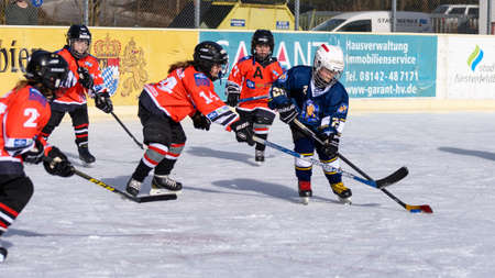 about age: Fuerstenfeldbruck, Bavaria, Germany - 06. February 2016: German Kids playing ice hockey. Age is about 10 years. Blue player surrounded by heavy defense near the goal.