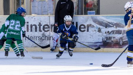 stumble: Fuerstenfeldbruck, Bavaria, Germany - 06. February 2016: German Kids playing ice hockey. Age is about 10 years. Blue Player just outmaneuvered the defense and is rushing to the goal.