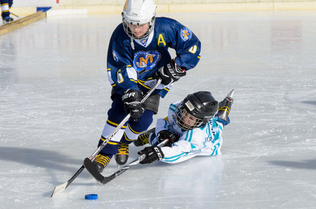 about age: Fuerstenfeldbruck, Bavaria, Germany - 06. February 2016: German Kids playing ice hockey. Age is about 10 years. Desperate last minute defense, but blue player goes through.