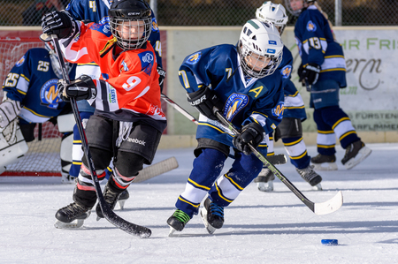 about age: Fuerstenfeldbruck, Bavaria, Germany - 06. February 2016: German Kids playing ice hockey. Age is about 10 years. Orange Player on the left is approaching for a defense action.