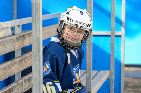 age 10: Fuerstenfeldbruck, Bavaria, Germany - 06. February 2016: German Kids playing ice hockey. Age is about 10 years. Player resting on the bench.