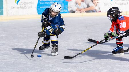 stumble: Fuerstenfeldbruck, Bavaria, Germany - 06. February 2016: German Kids playing ice hockey. Age is about 10 years. Players are fighting for the puck.