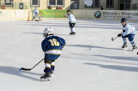 about age: Fuerstenfeldbruck, Bavaria, Germany - 06. February 2016: German Kids playing ice hockey. Age is about 10 years. Blue player starting a long run to the goal. Editorial