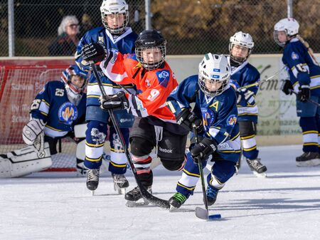 age 10: Fuerstenfeldbruck, Bavaria, Germany - 06. February 2016: German Kids playing ice hockey. Age is about 10 years. Orange Player on the left is approaching for a defense action.
