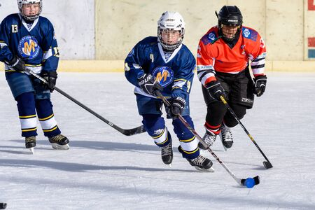 about age: Fuerstenfeldbruck, Bavaria, Germany - 06. February 2016: German Kids playing ice hockey. Age is about 10 years. Orange Player tries a defense, but blue player goes through. Editorial