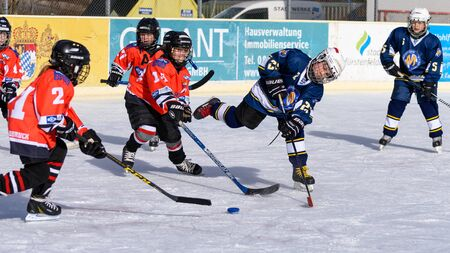 racket stadium: Fuerstenfeldbruck, Bavaria, Germany - 06. February 2016: German Kids playing ice hockey. Age is about 10 years. Orange Players trie a defense, but blue player goes through and shoots to the goal.