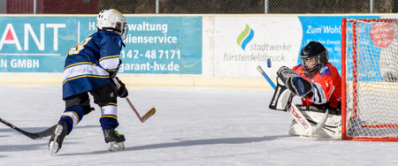about age: Fuerstenfeldbruck, Bavaria, Germany - 06. February 2016: German Kids playing ice hockey. Age is about 10 years. Blue Player is shooting  to the goal - puck still in the air.