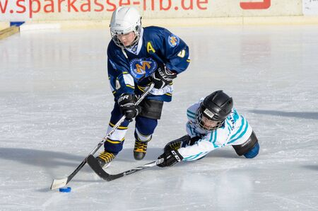 age 10: Fuerstenfeldbruck, Bavaria, Germany - 06. February 2016: German Kids playing ice hockey. Age is about 10 years. Desperate last minute defense, but blue player goes through.